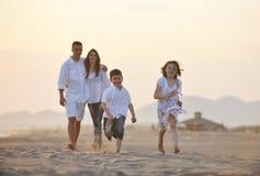 A família nova feliz tem o divertimento na praia no por do sol Fotos de Stock