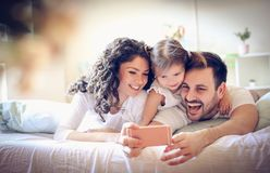 A família nova feliz toma um autorretrato com telefone esperto fotografia de stock