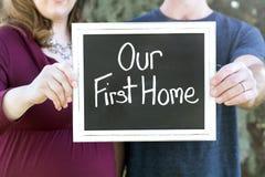 Família nova grávida que compra sua casa nova que guarda nosso primeiro sinal home foto de stock royalty free