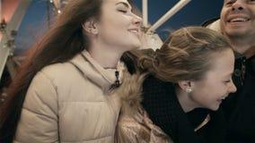 A família nova junto em um Ferris roda dentro um abraço Na noite na Luna Park, no pai, na mãe e na filha sobre filme