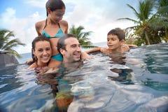 Família nova na piscina que passa o bom tempo Imagens de Stock Royalty Free