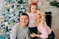 Família nova no fundo da árvore de Natal fotografia de stock royalty free
