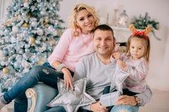 Família nova no fundo da árvore de Natal fotografia de stock