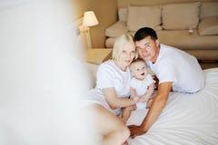 Família nova - pai, mãe e bebê relaxando na cama E Fotografia de Stock Royalty Free