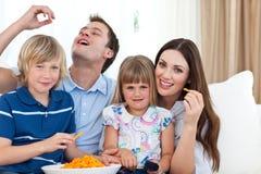 Família nova que come batatas fritas ao prestar atenção à tevê Fotografia de Stock