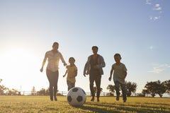 Família nova que corre após um futebol em um parque fotos de stock