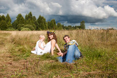 Família nova que descansa em um campo Fotografia de Stock