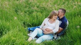 Família nova que descansa no prado verde A mulher está grávida filme