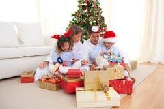 Família nova que desembala presentes de Natal Fotografia de Stock