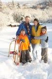 Família nova que está na paisagem nevado Fotografia de Stock