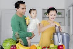 Família nova que faz o suco saudável em casa Fotos de Stock Royalty Free