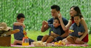 Família nova que joga a bolha de sabão no parque filme