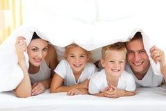 Família nova que joga junto em uma cama imagens de stock royalty free
