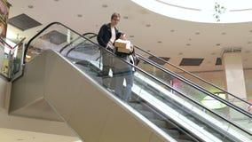 Família nova que monta uma escada rolante em um shopping com os sacos em suas mãos vídeos de arquivo