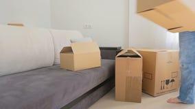 Família nova que move-se fora de seus apartamento velho e caixas levando da sala filme