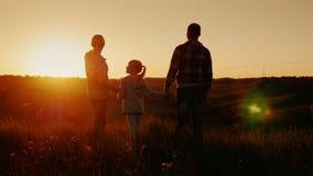 Família nova que olha para a frente ao horizonte no por do sol A mamã, o paizinho e a filha passam o tempo junto video estoque