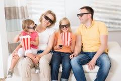 Família nova que olha a tevê 3d Fotografia de Stock Royalty Free