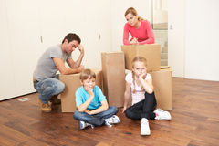 Família nova que olha a virada entre caixas Fotografia de Stock