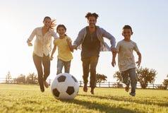 Família nova que persegue após um futebol em um parque foto de stock