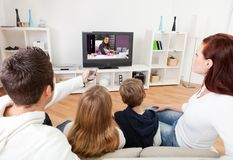 Família nova que presta atenção à tevê em casa Imagens de Stock Royalty Free