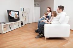 Família nova que presta atenção à tevê em casa Imagem de Stock