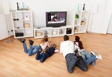 Família nova que presta atenção à tevê em casa Foto de Stock