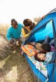 Família nova que relaxa dentro da barraca no feriado Fotos de Stock Royalty Free