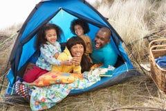 Família nova que relaxa dentro da barraca no feriado imagem de stock royalty free