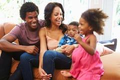 Família nova que relaxa em Sofa Together Imagem de Stock Royalty Free