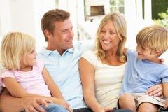Família nova que relaxa junto no sofá Fotos de Stock