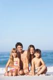 Família nova que relaxa no feriado da praia Fotos de Stock Royalty Free