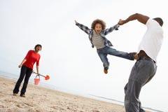 Família nova que relaxa no feriado de acampamento da praia Fotos de Stock Royalty Free
