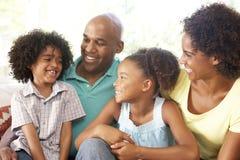 Família nova que relaxa no sofá em casa Fotos de Stock Royalty Free
