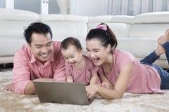 Família nova que ri com seu bebê Fotografia de Stock