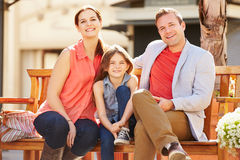 Família nova que senta-se em Seat na alameda junto fotografia de stock