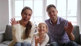 Família nova que senta-se nas mãos de ondulação do sofá que olham a câmera video estoque