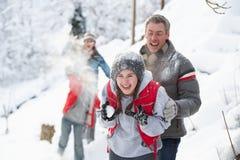 Família nova que tem a luta do Snowball foto de stock
