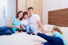 Família nova que tem o divertimento na cama Família feliz em casa Imagem de Stock Royalty Free