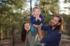 Família nova que tem o divertimento na natureza foto de stock