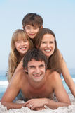 Família nova que tem o divertimento no feriado da praia Fotos de Stock Royalty Free