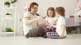 Família nova que tem o fim de semana do divertimento Pai que joga com duas crianças filme