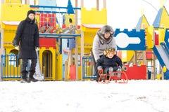 Família nova que toboganning para fora na neve imagem de stock royalty free