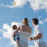 A família nova voa um papagaio na praia com bebê Imagens de Stock