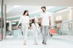 A família, o pai, a mãe e a filha estão andando a uma outra loja no shopping foto de stock
