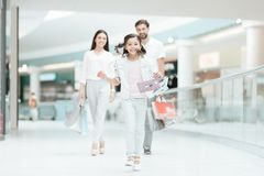 A família, o pai, a mãe e a filha estão andando a uma outra loja no shopping A menina está correndo foto de stock