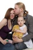 Família: o paizinho prende o bebê e beija a matriz Foto de Stock