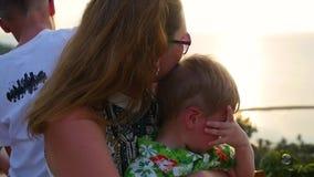 A família olha o mar e as montanhas de uma altura no tempo do por do sol Vista panorâmico filme