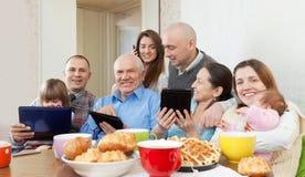 Família ou amigos felizes com dispositivos eletrónicos Foto de Stock Royalty Free