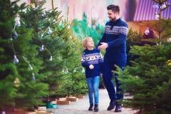 Família, pai feliz e filho escolhendo a árvore de Natal por feriados de inverno no mercado sazonal foto de stock royalty free