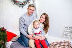 Família, pai, mãe e filho felizes, na manhã no quarto decorado para o Natal Eles para abraçar e ter o divertimento ` S do ano nov foto de stock